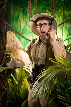 pith: Young retro explorer asking informations on the phone with vintage telephone in the jungle.