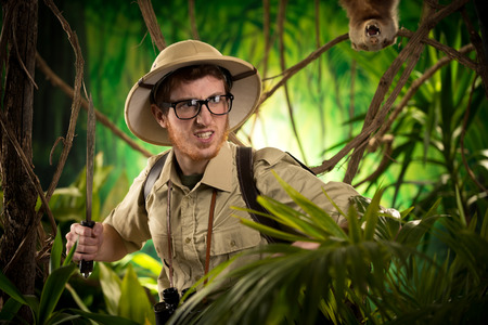 machete: Aggressive confident explorer walking in the jungle holding a machete with ferocious animal on background.