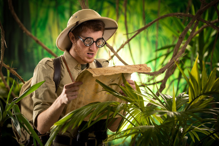 Lost explorer with glasses holding an old map looking for the right direction. photo