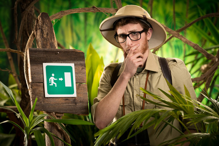 Lost young adventurer in the jungle thinking with hand on chin and exit sign.