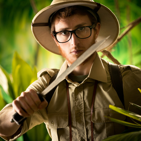 watchful: Watchful young adventurer holding a machete walking through the jungle.