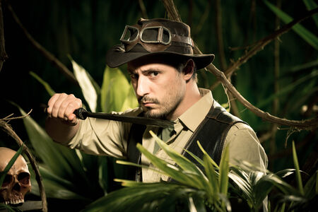 machete: Young confident adventurer in the jungle holding a machete and looking around. Stock Photo