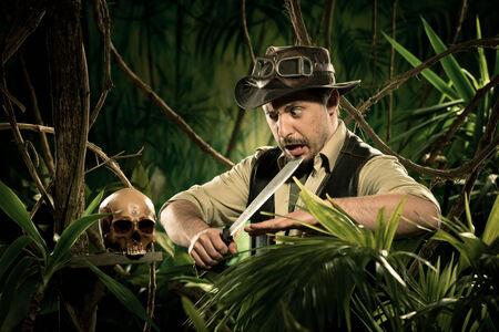 machete: Explorer with machete in the jungle discovering a human skull.