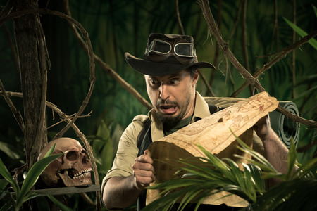 Explorer with old map in the jungle discovering a human skull. Stock Photo
