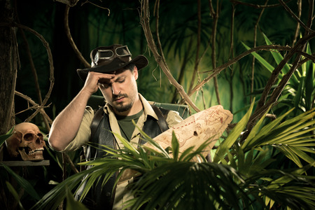 Young explorer lost in jungle examining an old map. photo