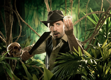 Adventurer with machete finding a huge gem in the jungle with skull on foreground.