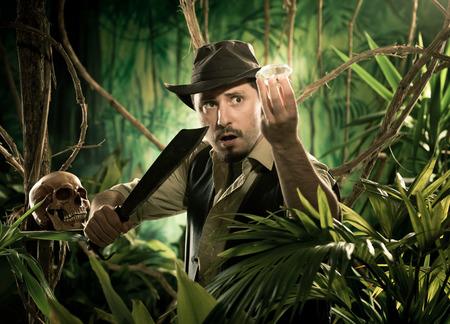 aventurero: Aventurero con machete encontrar una gran joya en la selva con el cr�neo en primer plano. Foto de archivo