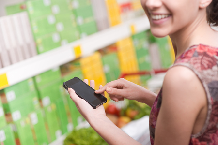 mobile shopping: Smiling young woman at supermarket using mobile phone and looking at camera.
