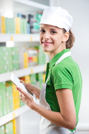 retailer: Smiling female sales clerk holding a digital tablet at supermarket.