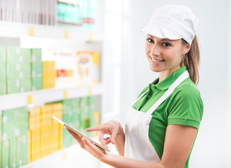 Smiling female sales clerk holding a digital tablet at supermarket. photo