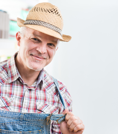 checked shirt: Smiling cheerful farmer posing in checked shirt and dungarees. Stock Photo
