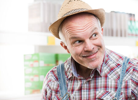 looking around: Funny farmer at supermarket making a face and looking around.