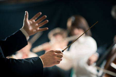conductor: Orchestra conductor directing symphony orchestra with performers on background, hands close-up. Stock Photo