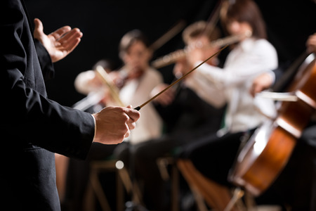 Conductor directing symphony orchestra with performers on background, hands close-up.