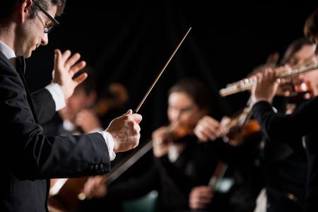 orquesta: Conductor dirigir la orquesta sinfónica con intérpretes en el fondo.