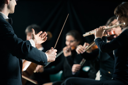 Conductor directing symphony orchestra with performers on background. Banque d'images