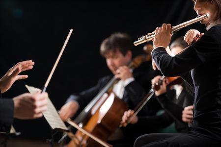 orquesta: Conductor dirigir la orquesta sinfónica en concierto con el flautista en primer plano.