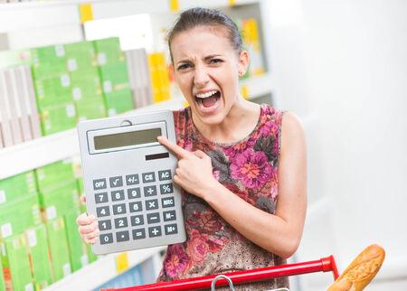 caras emociones: Mujer joven enojado gritando en el supermercado y que apunta a una calculadora.