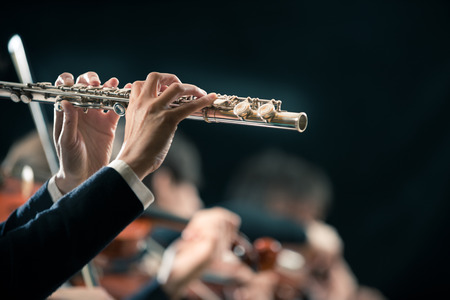 Female flutist close-up with orchestra performing on background. Stock Photo