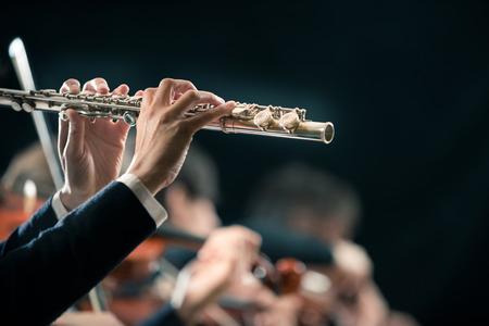 orquesta: Flautista Mujer de cerca con la orquesta tocando en el fondo. Foto de archivo