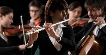 Vrouw fluitist close-up met orkest uitvoeren op de achtergrond. Stockfoto