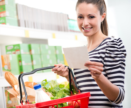 Woman at supermarket holding a full shopping basket and a shopping list. photo