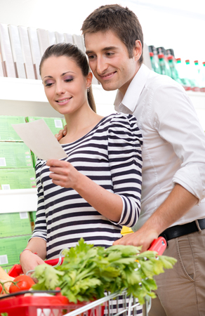 Attractive couple shopping at supermarket with shopping list. photo