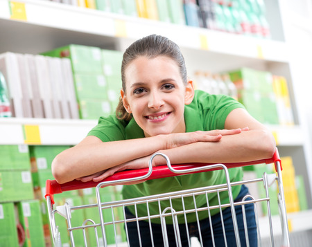 retail shopping: Smiling woman at supermarket leaning to a shopping cart with shelves on background. Stock Photo