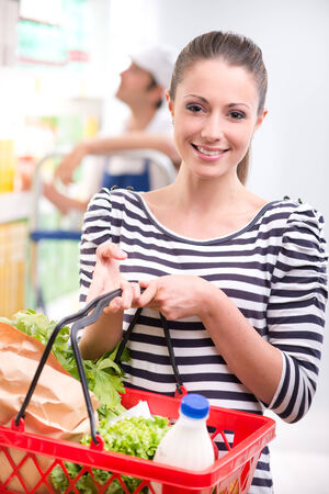 Attractive young woman smiling and holding a shopping basket at store. photo