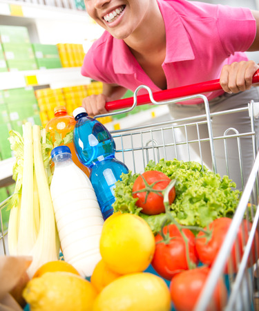 supermarket cart: Young woman in pink shirt leaning to a shopping cart at supermarket. Stock Photo