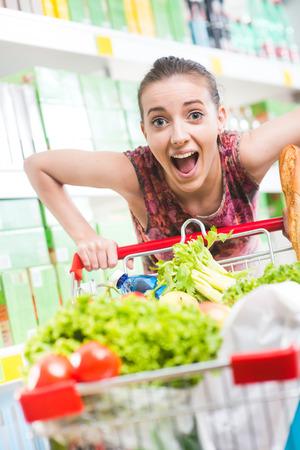 gasping: Woman gasping and pushing a full shopping cart at supermarket.