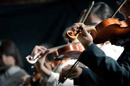 Symphony orchestra violinists performing on stage against dark background. Stock Photo
