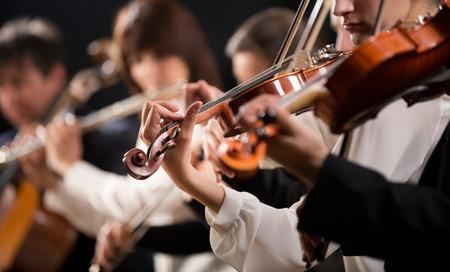 어두운 배경에서 수행 심포니 오케스트라 첫번째 바이올린 섹션을 참조하십시오.