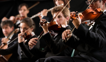 Symphony orchestra first violin section performing on dark background.