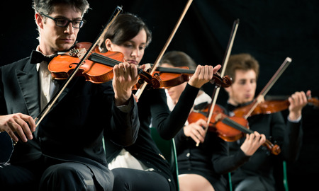 Violin orchestra performing on stage on dark background. photo