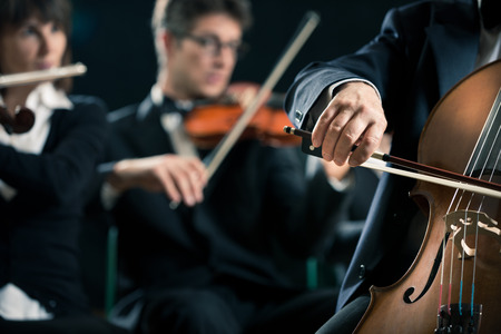 a symphony: Symphony orchestra performing with cello player hand close-up.