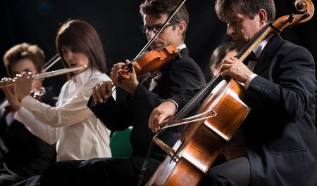 Symfonie orkest op het podium, violen, cello en fluit uitvoeren.