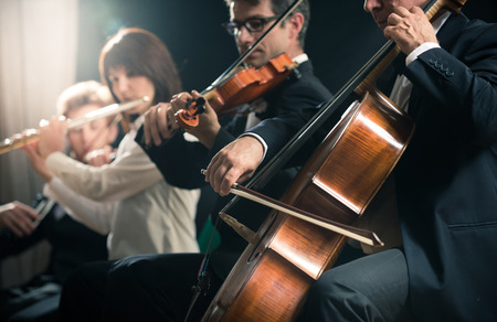 violins: Symphony orchestra on stage, violins, cello and flute performing. Stock Photo
