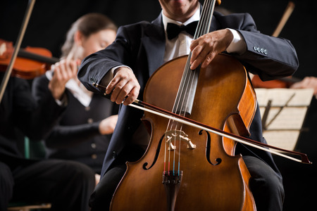 musical instrument: Cello professional player with symphony orchestra performing in concert on background.