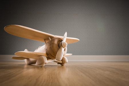 Wooden toy plane hand carved model on hardwood floor. 스톡 콘텐츠