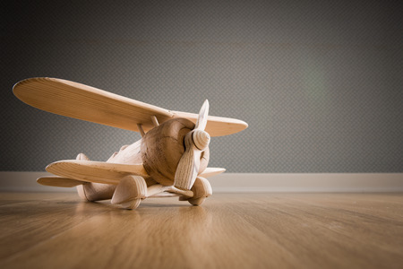 Wooden toy plane hand carved model on hardwood floor. Stockfoto