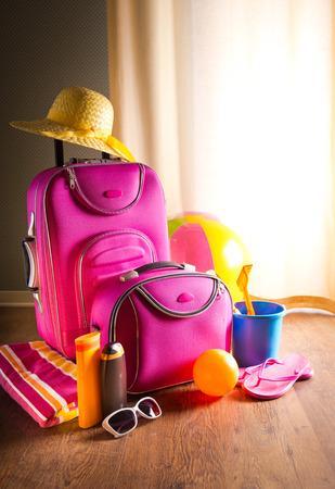 femme valise: Vacances d'�t� fond avec un sac rose, cr�me solaire, tongs et des jouets de plage.