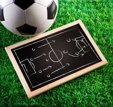 tactic: Blackboard with game tactics with soccer ball and green turf on background. Stock Photo