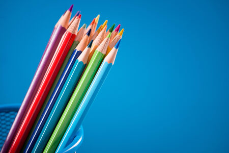 Colorful wooden pencils set against cyan bright background. photo