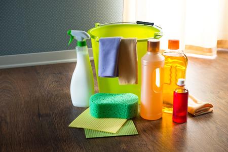 Productos de limpieza y detergentes de madera en el suelo con cuchara, guantes, tela y esponjas.