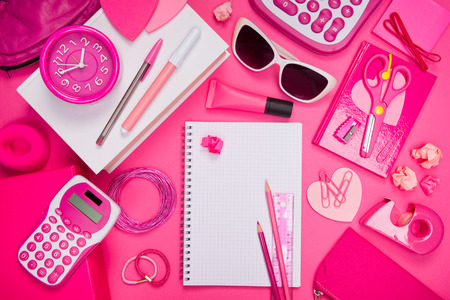 Girly pink desktop and stationery with blank notebook and pencil. photo