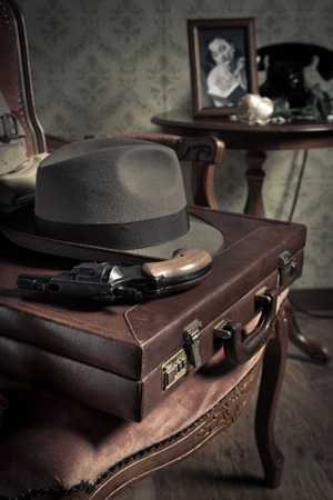 Detective equipment with briefcase, hat and gun, vintage interior on background.