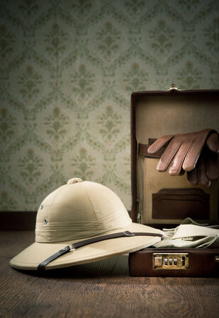Explorer packing with open leather briefcase, pith hat, leather gloves on wooden surface.