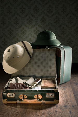 Open suitcase with colonial style explorer equipment including pith helmet, old books and brass telescope.