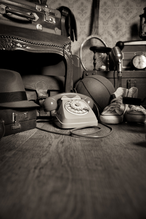 rarity: Group of vintage objects on attic hardwood floor, including old toys, phone and sports items. Stock Photo